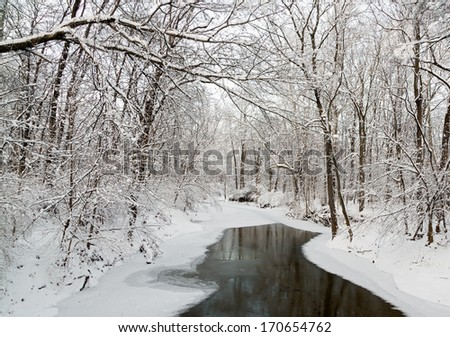 Snow covers the trees around a partially frozen creek in mid winter. - stock photo