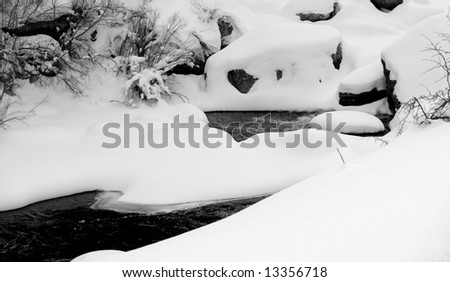 Snow drifts create unusual shapes over the boulders of a mountain river in Colorado. - stock photo