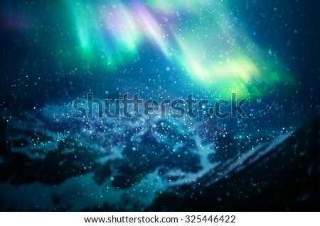 Snow falling against aurora borealis - focus on snowflakes, northern lights and mountains in the background - stock photo