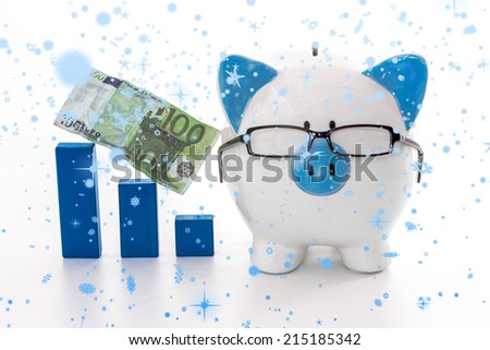 Snow falling against piggy bank wearing glasses with blue graph model and hundred euro note - stock photo