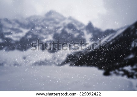 Snow falling against winter mountain landscape - focused on snowflakes - stock photo