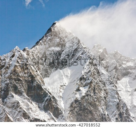 Snow flags on the top of the Lhotse (8516hm) on the background of blue sky - Everest region, Nepal, Himalayas - stock photo