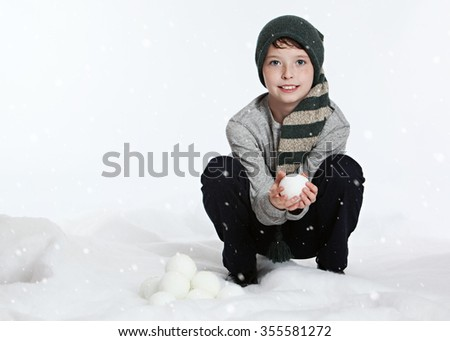 Snow fun.  Adorable young boy playing in the 'snow' and holding a 'snowball'.   - stock photo