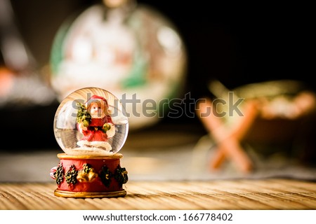 Snow globe in front of christmas ornaments close up - stock photo