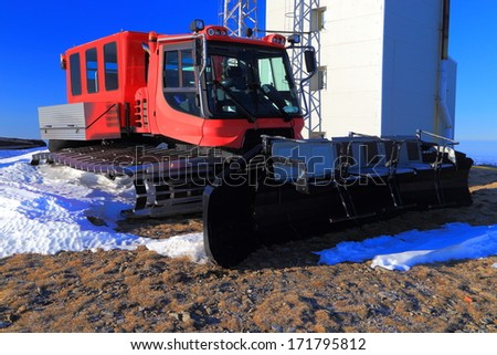 Snow grooming machine waiting for the snowfall on top of the mountain - stock photo