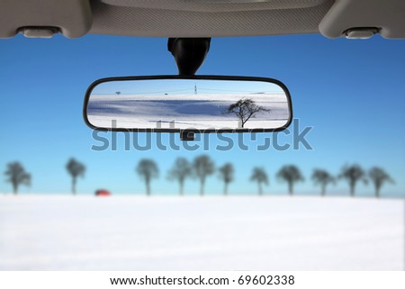 Snow landscape reflected in the car rear view mirror - stock photo