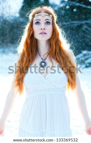 Snow Maiden. Whimsical image of beautiful red head woman standing in snow looking angelic - stock photo