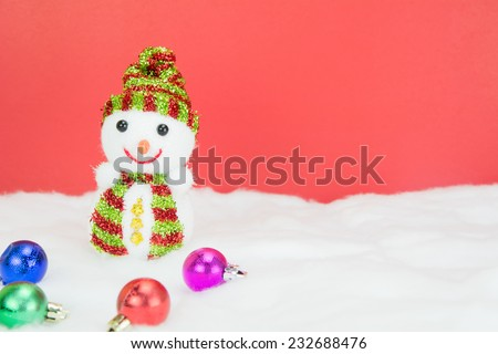 Snow man and christmas balls  on white snow on red background, concept christmas