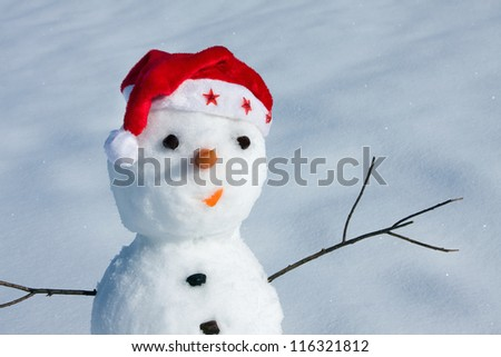 Snow man in santa cap on nature in sunny cold day - stock photo