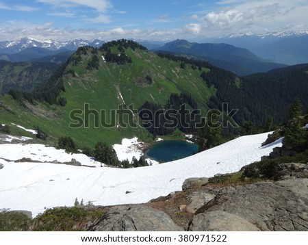 Snow melting around Sauk Lake - stock photo