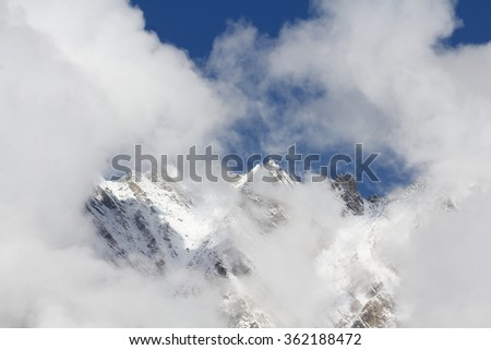 Snow mountain in cloud background. Winter landscape in Hunza valley, Pakistan. overlay cloud on top of snow mountain and blue sky. - stock photo