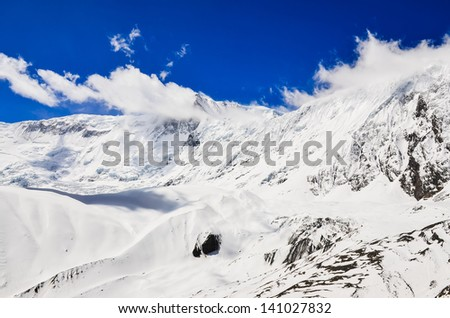 Snow mountain peak with clouds and blue sky, Himalayas, Nepal - stock photo