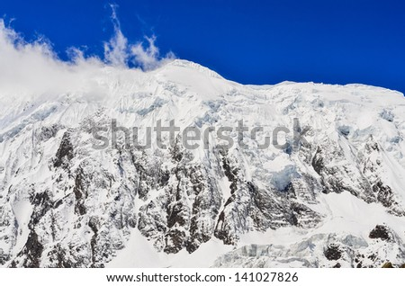 Snow mountain peak with glacier, clouds and blue sky, Himalayas, Nepal - stock photo