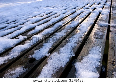 snow on a wooden dock