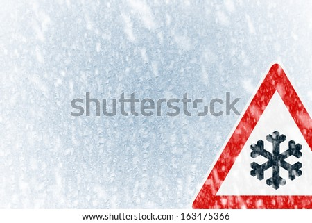 Snow on an ice covered windshield with warning sign and copy space.  - stock photo