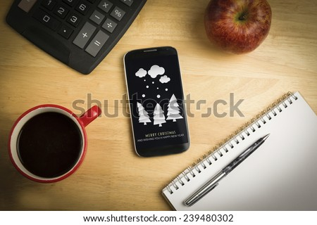 Snow on fir trees against overhead of smartphone with pen - stock photo