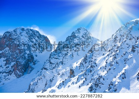 Snow on high mountain rocky peaks in Andorra - stock photo
