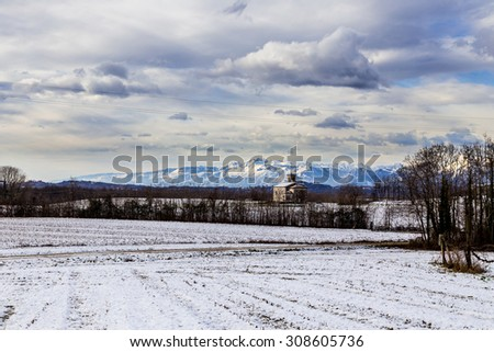 snow on the fields next to a medieval church in the italian countryside