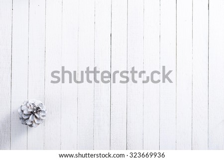 snow painted pine cone on rustic white wood table, Christmas decoration background - stock photo