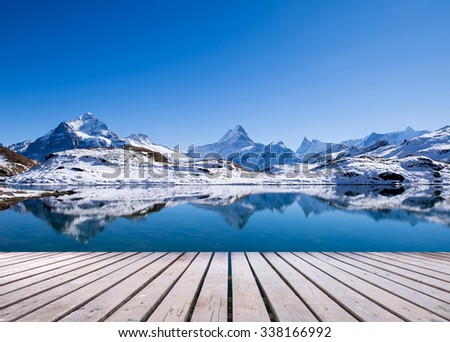 snow peaks of Jungfrau region grindelwald switzerland with wooden terrace - stock photo