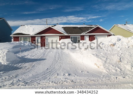 Snow piled up along a plowed road in a northern suburb. - stock photo