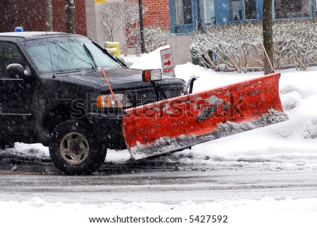 Snow plow truck on a road during a snowstorm - stock photo