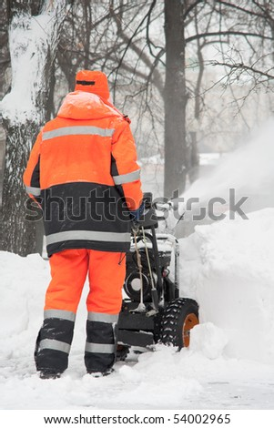Snow removal with a snow blower - stock photo