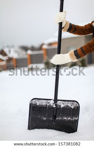 Snow shovel in female hands on a winter day - stock photo