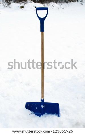 snow shovel stuck in the pile of snow - stock photo