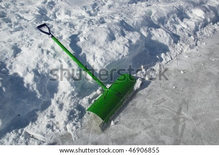 Snow shovel used for clearing ice on outdoor skating rink. - stock photo