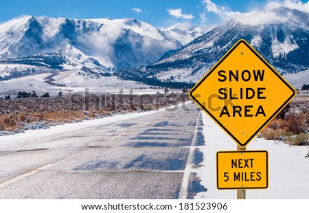 Snow Slide Area Sign:  Motorists are warned of dangerous driving conditions on a road leading into the Sierra Nevada Mountains.  - stock photo