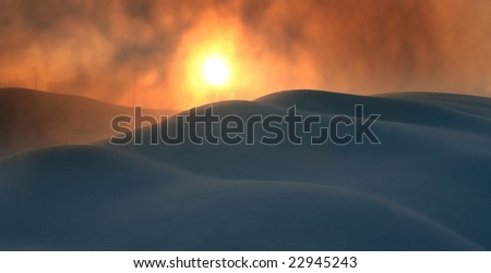 Snow snowstorm with snow drifts against a rising sun. - stock photo