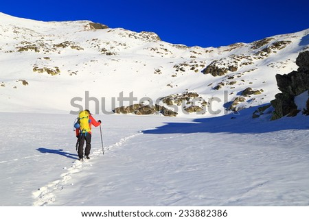 Snow trail and winter climber on the mountains in sunny day - stock photo
