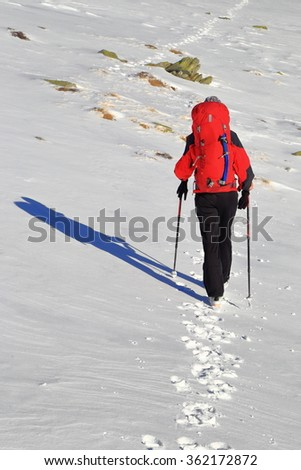 Snow trail and woman backpacker walking on the mountain in winter, Retezat massif, Romania - stock photo