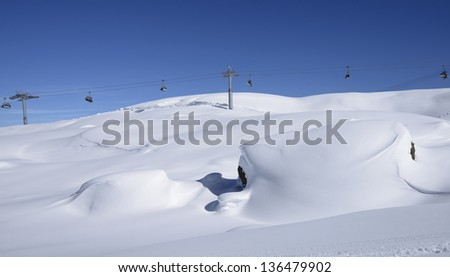 snow waves and chair lift, Arabba; bright snow covers stones in slope in Dolomites in background chair lift, shot under deep blue sky