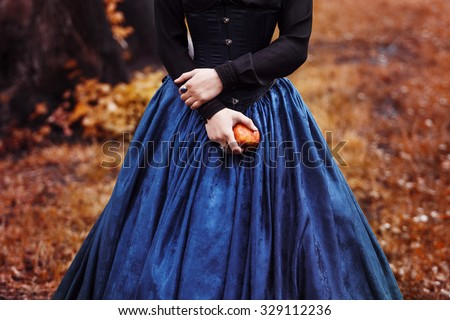 Snow White princess with the famous red apple. Girl holds a ripe Apple sitting on lap - stock photo
