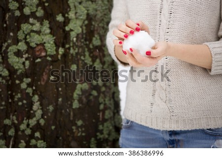 Snowball in hands of a young woman with red manicure and warm sweater. Winter walks outdoors. Snow in the forest. - stock photo