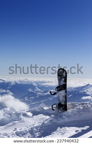 Snowboard in snow on off-piste slope at sun day. Caucasus Mountains, Georgia. Ski resort Gudauri. - stock photo
