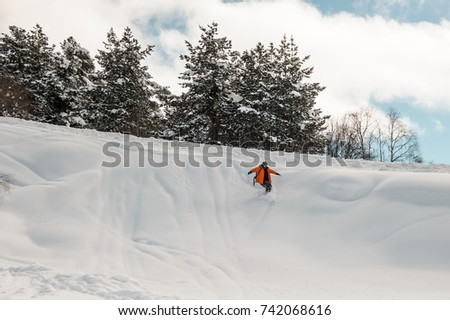 Snowboard rider descending down the snow slope on the background of trees and cloudy sky