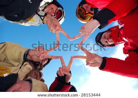 Snowboard team making a finger star in the blue ski as background - stock photo