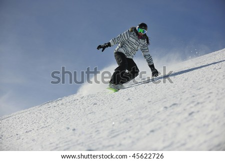 snowboard woman racing downhill slope and freeride on powder snow at winter season and sunny day - stock photo