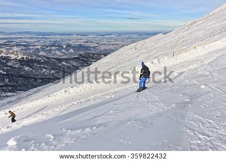 Snowboarder and Downhill Skier in Kasprowy Wierch in Zakopane in winter. Zakopane is a town in Tatra Mountains. Kasprowy Wierch is a mountain in Zakopane and the most popular ski area in Poland - stock photo