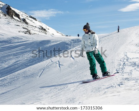 Snowboarder at a ski resort in the mountains  - stock photo