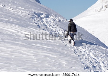 Snowboarder climbing a snowy mountain, freeride - stock photo