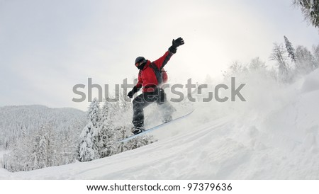 Snowboarder doing a jump and free ride on  powder snow at winter season - stock photo