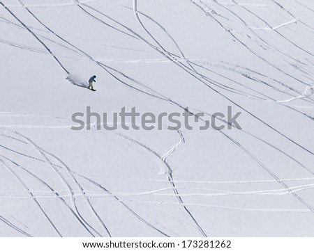 Snowboarder downhill on off piste slope with newly-fallen snow. Caucasus Mountains, Georgia, ski resort Gudauri.