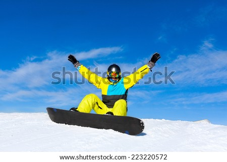snowboarder excited happy raised arms hands up sitting on snow mountain slope copy space blue sky