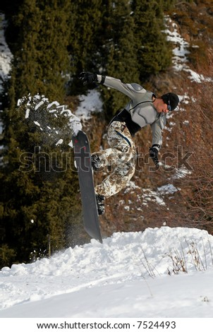 Snowboarder extreme jump on ski slope - stock photo