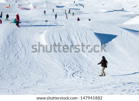 Snowboarder going down the slope at a snowpark in Madonna di Campiglio in Italian Alps