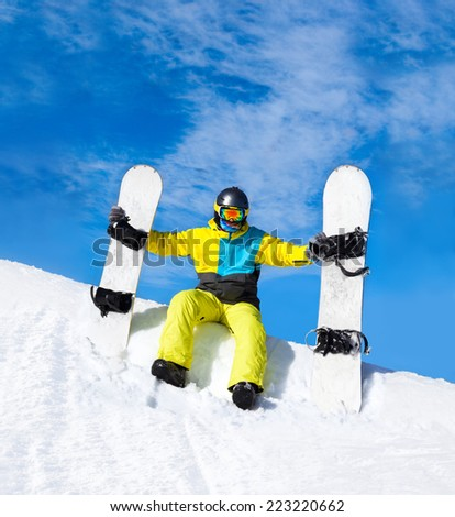 snowboarder hold two snowboards sitting on snow mountain slope copy space blue sky